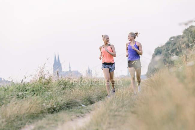 Две молодые женщины бегут по полевой дорожке — стоковое фото