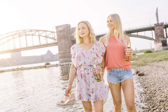 Frauen laufen mit Bierflaschen am Flussufer — Stockfoto