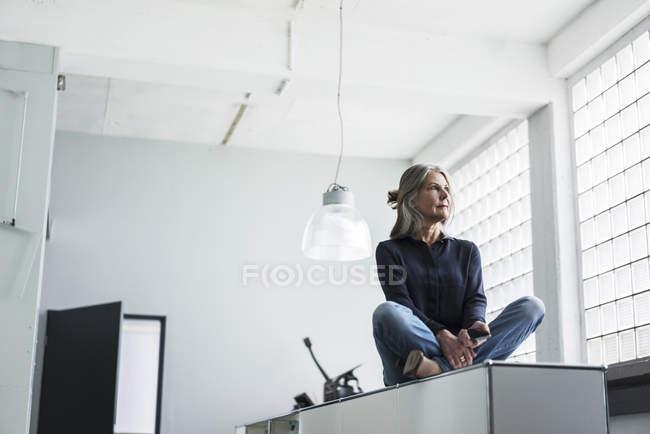 Ältere Frau sitzen auf einem Schrank — Stockfoto