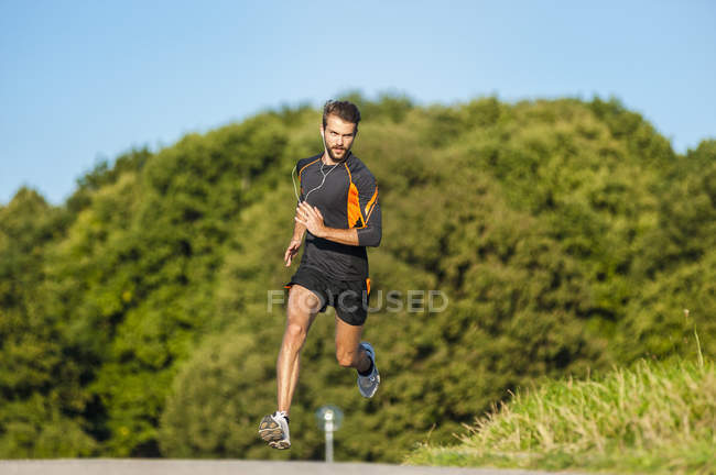 Active man running on rural path — Stock Photo