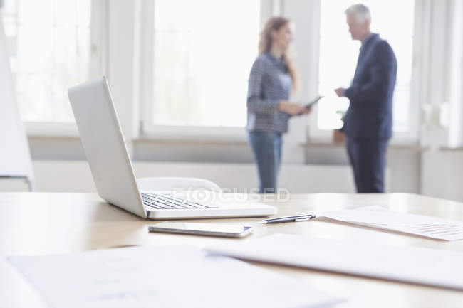 Laptop and documents on desk with business people — Stock Photo