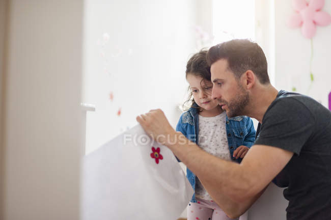 Father with daughter decorating wall in children room — Stock Photo