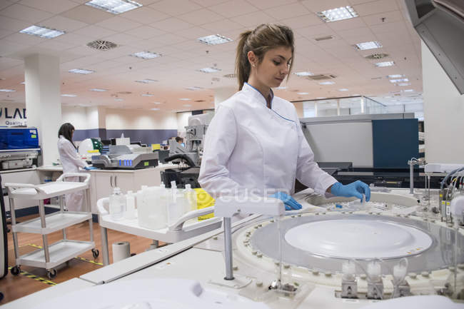 Laboratory technician in analytical laboratory using autoanalyzer — Stock Photo