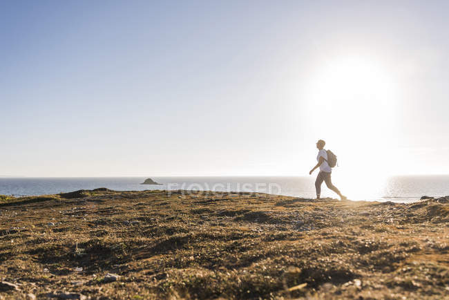 Woman with backpack walking on sandy coast at Finistere of Brittany, Crozon peninsula, France — Stock Photo