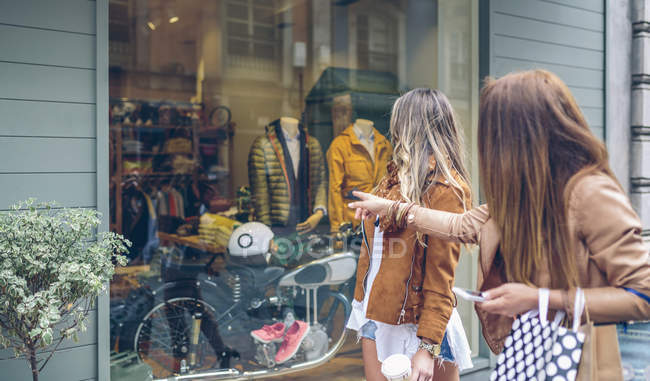 Two women looking at shop window of a boutique — Stock Photo