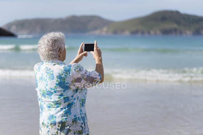 Senior woman on beach taking picture — Stock Photo
