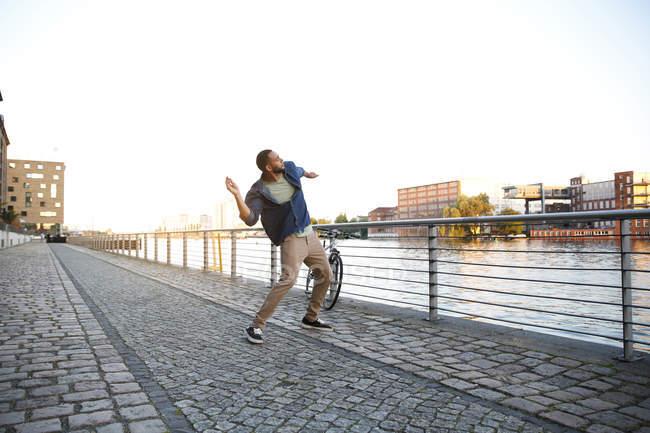Giovane uomo gettando pietra nel fiume — Foto stock