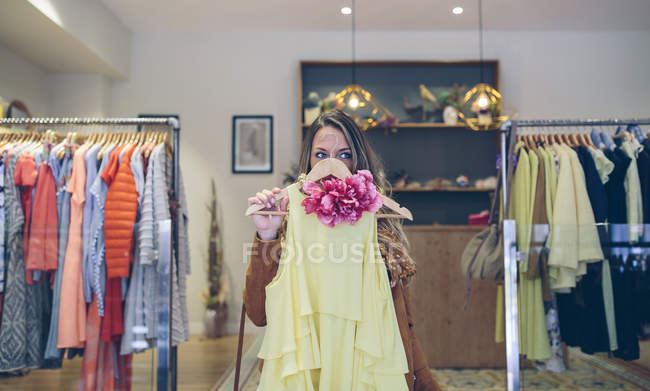 Woman holding dress in a boutique — Stock Photo