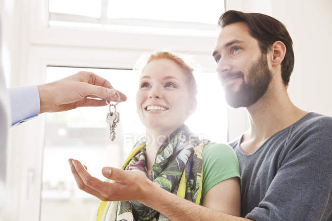 Young couple receiving house key from real estate agent — Stock Photo