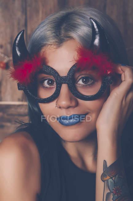 Ritratto di giovane donna sorridente che indossa occhiali di Halloween — Foto stock