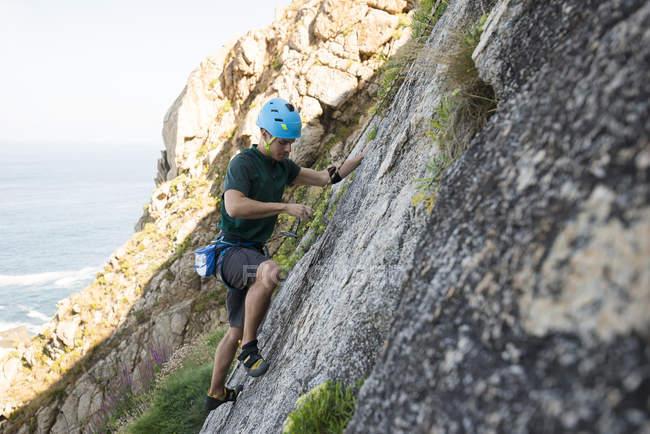 Молода людина сходження кам'яну стіну — стокове фото