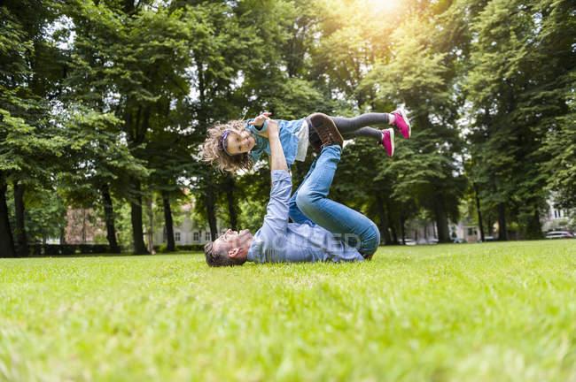 Padre sollevamento figlia sdraiato sull'erba giocare sul prato nel parco — Foto stock