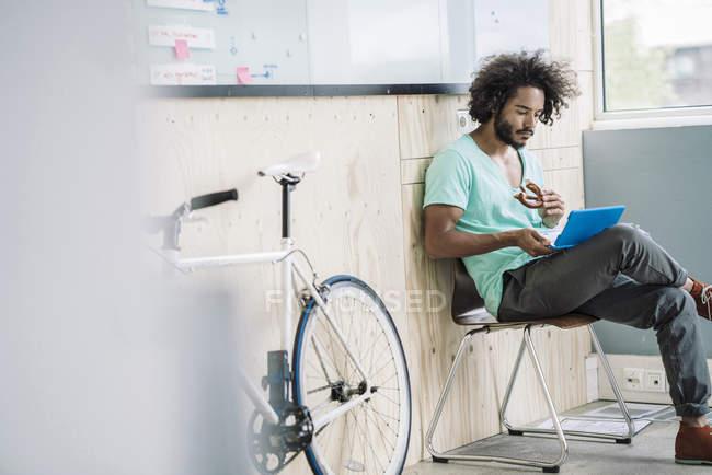 Дизайнер сидячи на стільці і використання ноутбука — стокове фото