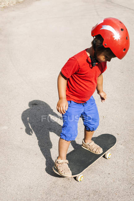 Little boy with red safety helmet standing on skateboard — Stock Photo