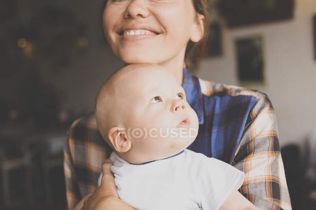 Smiling mother holding baby boy — Stock Photo