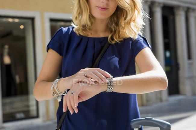 Femme blonde vérifiant l'heure, vue partielle — Photo de stock
