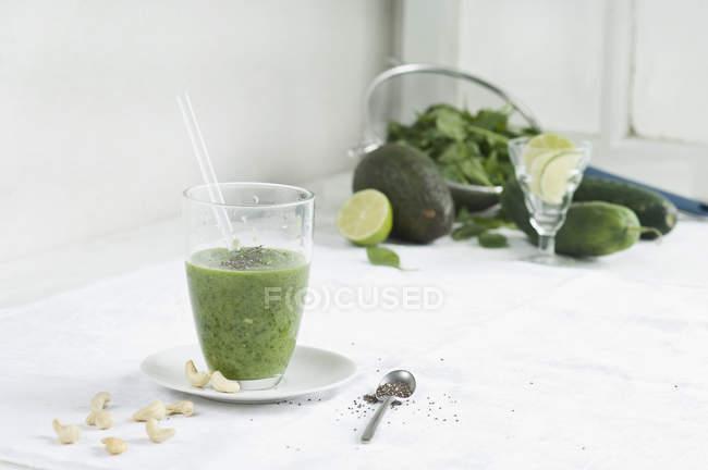 Batido verde de cristal con ingredientes - foto de stock