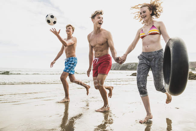 Friends running with a ball and tyre on the beach — Stock Photo