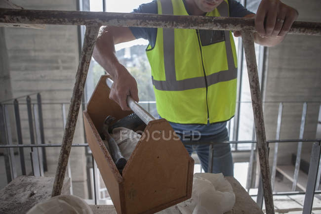 Construction worker carrying box on construction site — Stock Photo