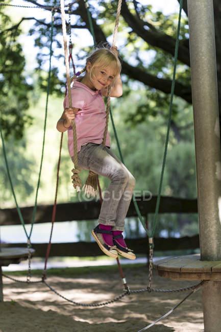 Fille escalade sur aire de jeux — Photo de stock