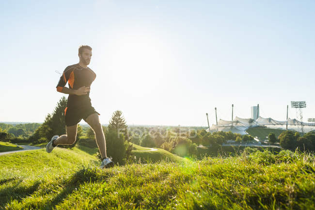 Sportive man running on meadow in park — Stock Photo