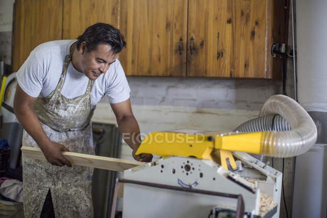 Man cutting wood in workshop — Stock Photo