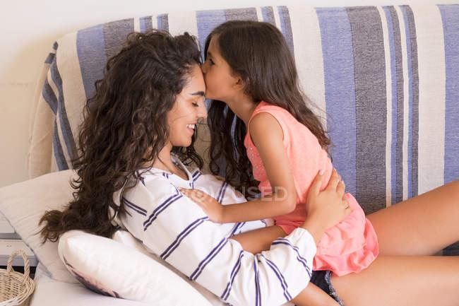 Piccola ragazza che bacia sorella adolescente — Foto stock