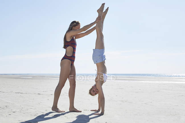 Young woman helping friend doing a handstand on the beach — Stock Photo
