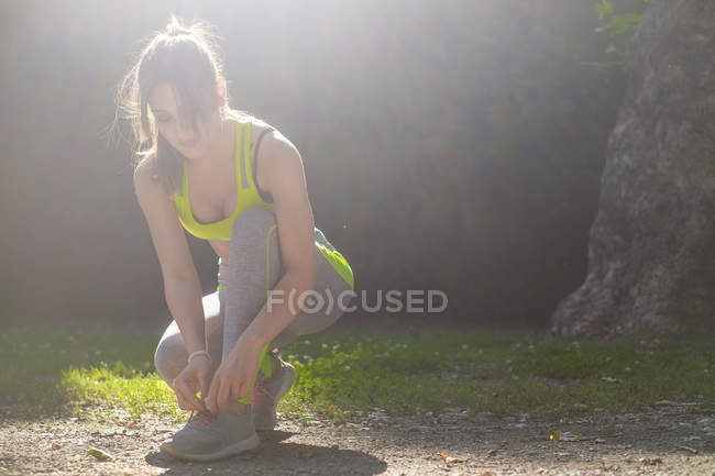 Sportswoman lacing her shoes in park — Stock Photo