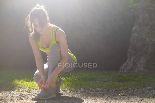 Спортсменка шнурует свои туфли в парке — стоковое фото