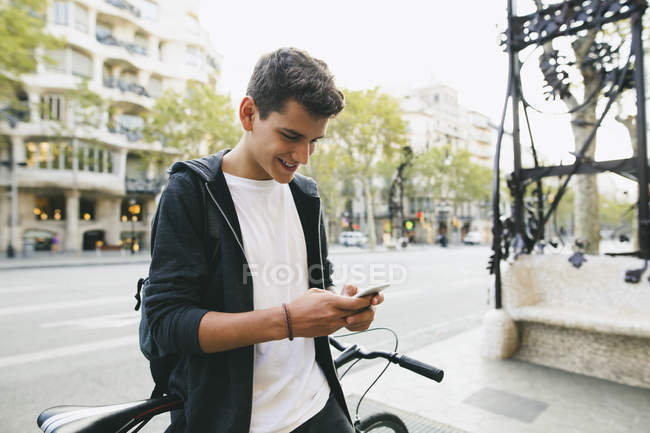 Teenager with a bike in the city, using smartphone, smiling — Stock Photo