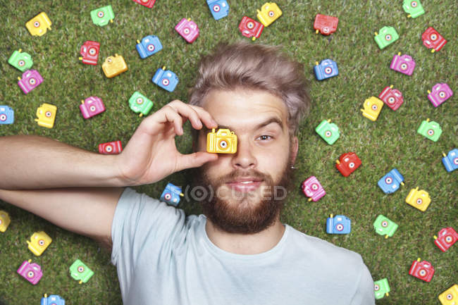 Young man lying on green grass with toy cameras — Stock Photo