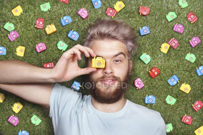 Молода людина лежала на зеленій траві з іграшку камер — стокове фото