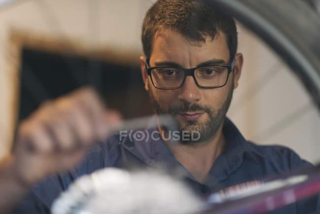 Portrait of mechanic in repair shop repairing bicycle — Stock Photo