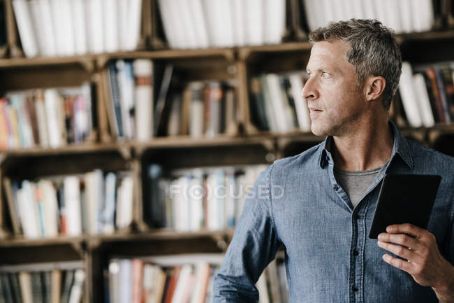 Mature man holding e book — Stock Photo
