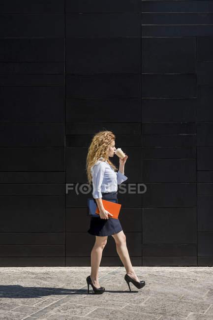 Businesswoman holding coffee to go — Stock Photo