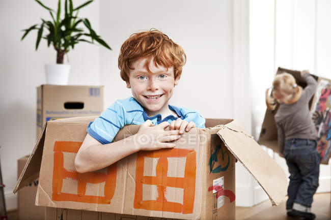 Happy boy looking out of a cardboard box in new apartment with sister on background — Stock Photo
