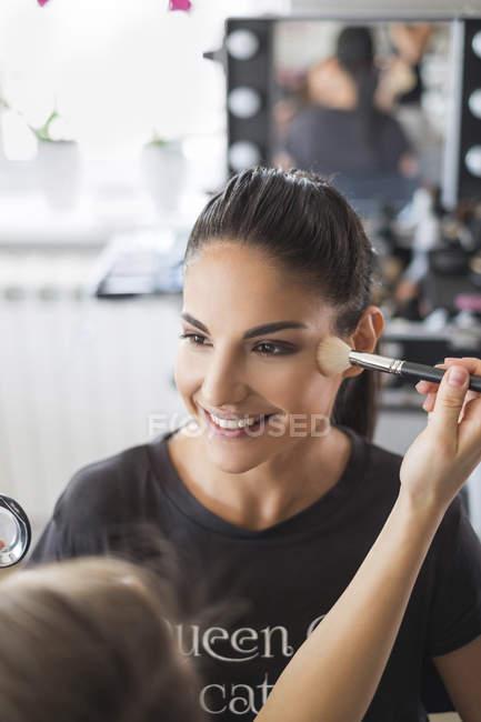 Close-up of visagiste styling customer in beauty studio — Stock Photo