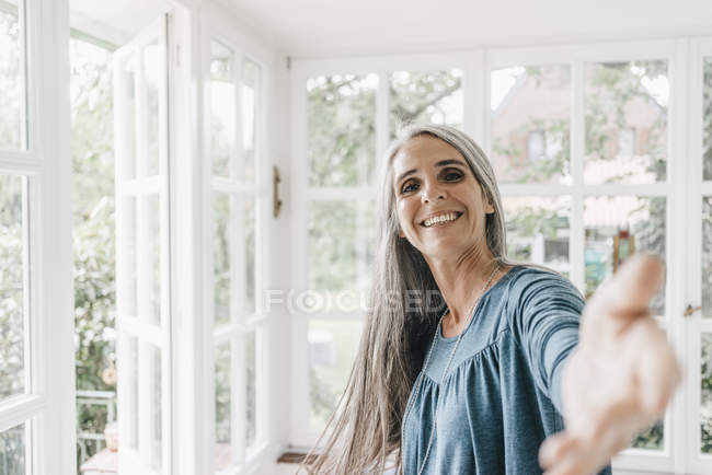 Woman inviting in winter garden — Stock Photo
