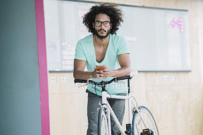 Man leaning on bicycle and using smartphone — Stock Photo