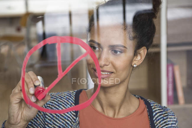 Woman drawing symbol on glass pane in office — Stock Photo
