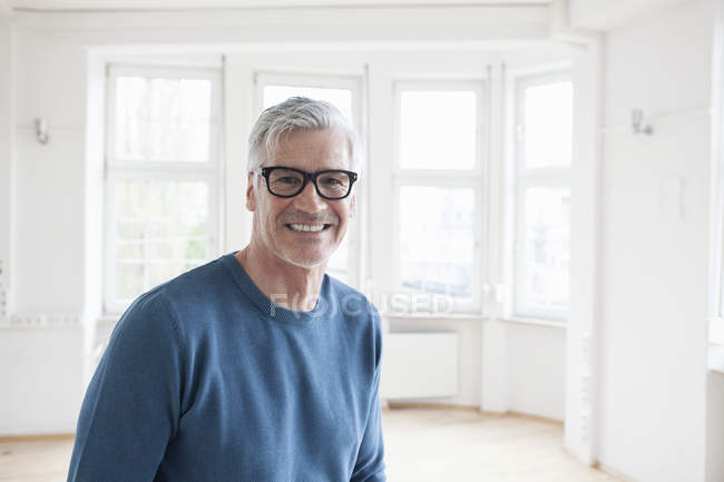 Portrait of smiling man in empty apartment — Stock Photo