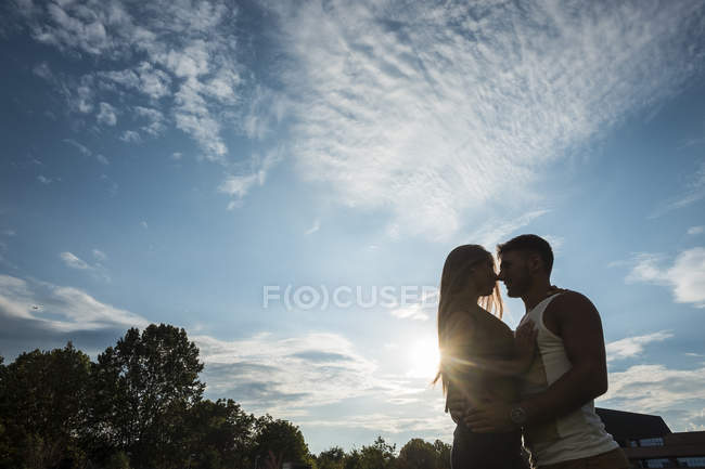 Young couple outdoors at sunset — Stock Photo