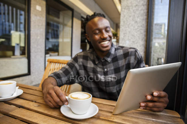 Hombre sentado en la cafetería y el uso de tabletas - foto de stock