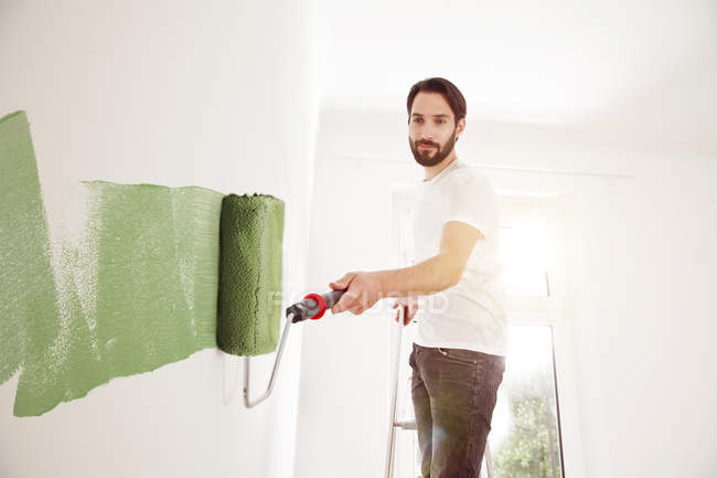 Young man painting wall green — Stock Photo