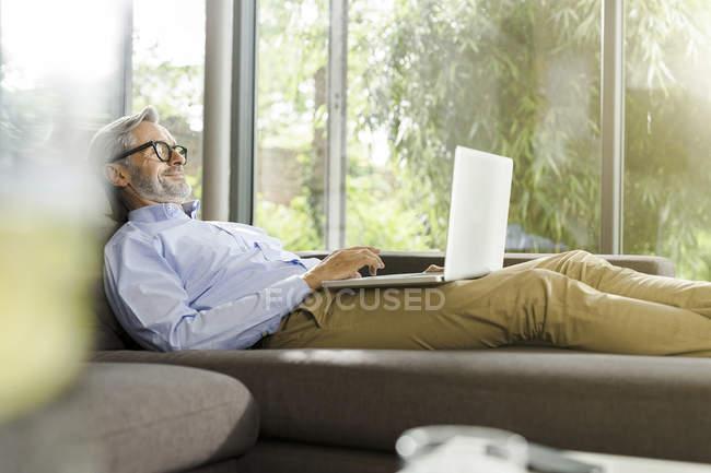 Uomo sorridente sdraiato sul divano nel suo soggiorno utilizzando il computer portatile — Foto stock