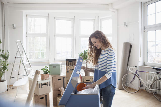 Woman in new apartment unpacking cardboard boxes — Stock Photo