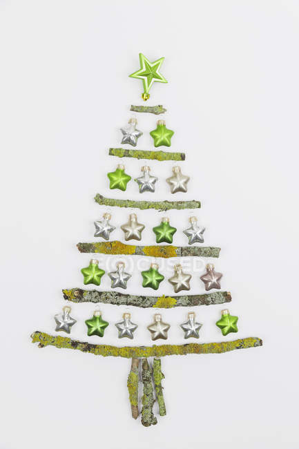 Christmas tree shaped of mossy branches and Christmas decorations — Stock Photo