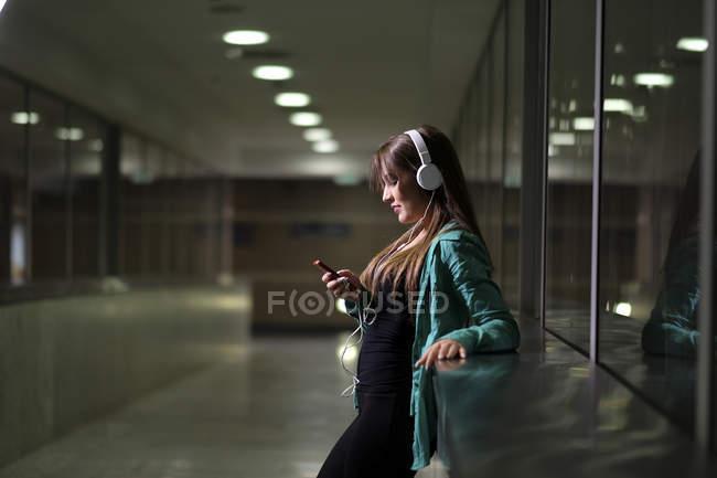 Mujer joven con auriculares y smartphone - foto de stock