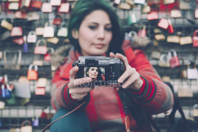 Germania, Colonia, donna che si fa selfie davanti a serrature d'amore a Hohenzollern Bridge — Foto stock